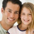 Man and young girl in living room smiling — Stock Photo #4768340