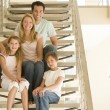 Family sitting on staircase smiling — Stock Photo #4768353