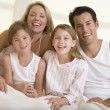 Family sitting in bed smiling - Stock Photo
