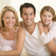 Family sitting in bed smiling — Stock Photo