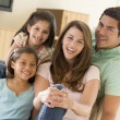 Family sitting in living room smiling — Stock Photo #4768375