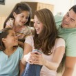 Family sitting in living room smiling — Stock Photo #4768376