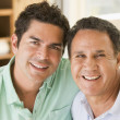 Two men in living room smiling - Stock Photo