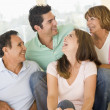 Two couples sitting in living room smiling and laughing — Stock Photo #4768396