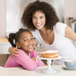 Woman and young girl in kitchen with cake and coffee smiling — Stock Photo