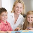 Woman and two young children in kitchen with art project smiling — Stock Photo