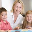 Woman and two young children in kitchen with art project smiling — Stock Photo #4768407