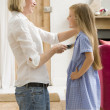 Woman in front hallway brushing young girl's hair and smiling — Stock Photo