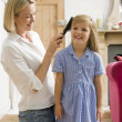 Woman in front hallway brushing young girl's hair and smiling - ストック写真