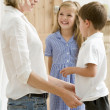Woman in front hallway with two young children smiling — Stock Photo #4768417