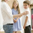 Woman in front hallway with two young children smiling — Stock Photo #4768419