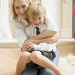 Woman in front hallway hugging young boy and smiling — Stock Photo