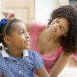 Woman in front hallway fixing young girl's hair and smiling — Stock Photo #4768424