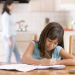 Young girl in kitchen doing homework with woman in background — Stock Photo