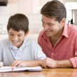 Man helping young boy in kitchen doing homework and smiling — Stock fotografie