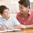 Man helping young boy in kitchen doing homework and smiling — Stock Photo