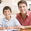 Photo: Man helping young boy in kitchen doing homework and smiling