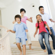 Family running down staircase smiling — Stock Photo #4768439