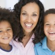 Woman and two young children smiling — Stock Photo