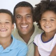 Man and two young children sitting in living room smiling — Stock Photo #4768448