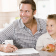 Man and young boy in kitchen with newspaper apple and coffee smi — Stock Photo