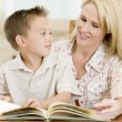 Woman and young boy reading book in dining room smiling — Stock Photo