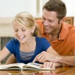 Man and young girl reading book in dining room smiling - Stock fotografie