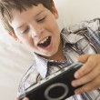 Young boy with handheld game indoors — Stock Photo