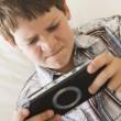 Stock Photo: Young boy with handheld game indoors looking unhappy