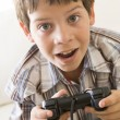 Young boy holding video game controller - Stock Photo
