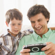 Man and young boy with handheld game smiling — Stock Photo #4768485