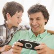 Man and young boy with handheld game smiling — Stock Photo #4768487