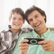 Man and young boy with handheld game smiling — Stock Photo #4768488
