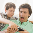 Stock Photo: Young boy taking handheld game from unhappy man