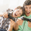 Man and young boy with video game controllers smiling - Foto Stock