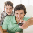 Man and young boy with remote control smiling — Stock Photo