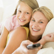 Woman and young girl with remote control embracing on sofa smili — Stock Photo
