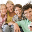 Family in living room with remote control smiling — Stockfoto