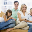 Family sitting in living room with remote control smiling - Foto de Stock  