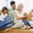 Family sitting in living room with digital camera smiling — Stock Photo #4768509