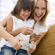 Woman and young girl in living room with video game controllers - Stok fotoğraf