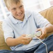 Young boy in living room with video game controller smiling - Stock Photo