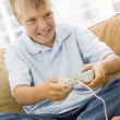 Young boy in living room with video game controller smiling — Stock Photo