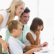 Family in home office using computer smiling — Stock Photo