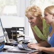 Woman and girl in home office with computer smiling — Stock Photo
