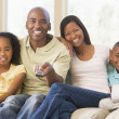 Family sitting in living room with remote control smiling — Stockfoto