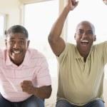 zwei männer im wohnzimmer jubel und lächeln — Stockfoto