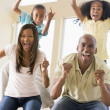 Family in living room cheering and smiling — Stockfoto