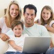 Family in living room with laptop smiling — Stock Photo