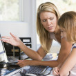 Stock Photo: woman and young girl in home office with computer looking unhapp